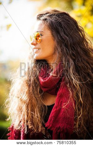 smiling young woman with long curly hair wearing  sunglasses and red scarf outdoor autumn portrait, profile