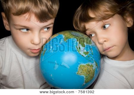 Boy And Girl In White T-shirts Steadfastly Looking At Globe