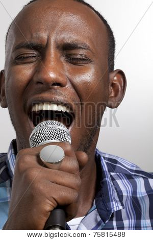 african man with ring sing a song with a microphone