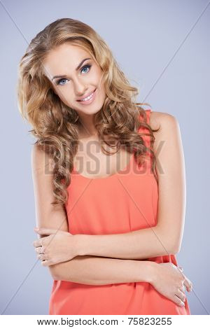 Close up Pretty Curly Long Hair Woman in Dark Peach Sleeveless Top Crossing Arms at Waistline While Looking at the Camera. Isolated on Gray Background.