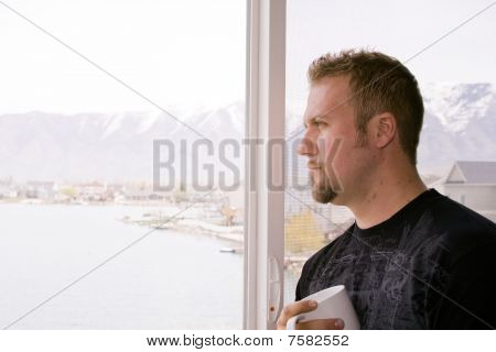 Man By The Window With A Cup Of Coffee