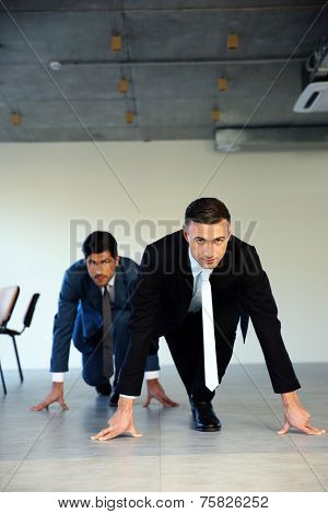 Two businessmen getting ready for corporate race - rat race concept