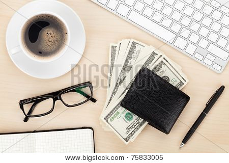 Office table with pc, supplies, coffee cup and money cash. View from above