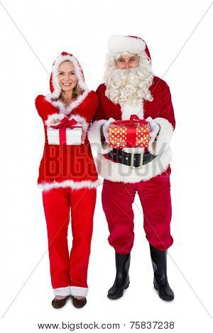Santa and Mrs Claus smiling at camera offering gift on white background
