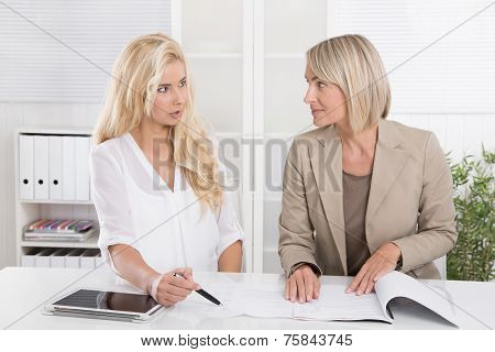 Two blond successful attractive businesswoman working in a team analyzing business papers.