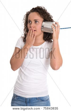 Shocked and surprised isolated young woman listening on tin can phone.