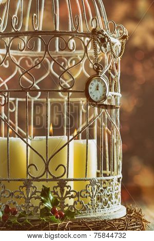 Pocket watch showing midnight on birdcage filled with candles