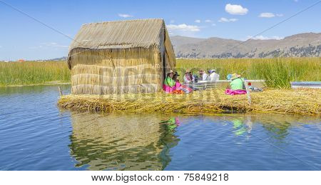PUNO, PERU, MAY 5, 2014: Local people sits in front of their reed made hut on one of Uros Islands (Lake Titicaca)