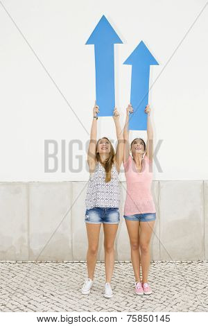 Beautiful and happy teenagers pointing blue arrows to the sky