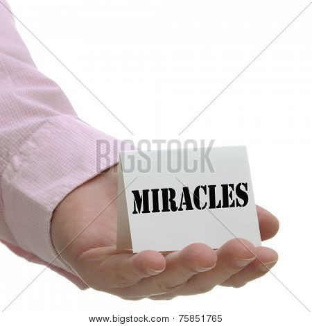 Business man holding miracles sign on hand