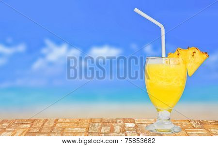 Glass of Fresh Pineapple Juice On A Table Near The Beach