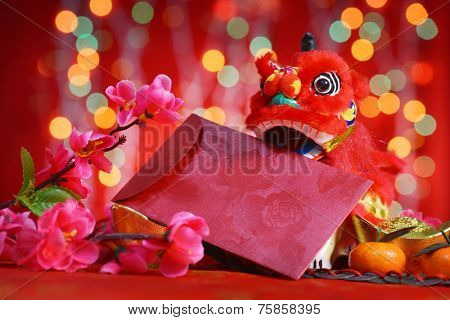 Chinese new year festival decorations, miniature dancing lion and ang pow or red packet with copy space ready for text, on glitter red background.