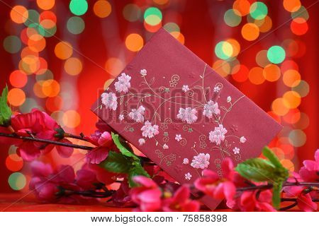 Chinese new year festival decorations, ang pow or red packet and plum flower.