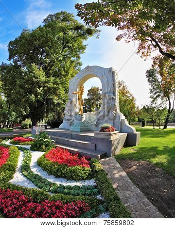 Elegant marble arch frames the bronze statue of Johann Strauss. Wonderful park in the center of Vienna