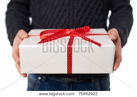 Male hands holding giftbox tied by red ribbon