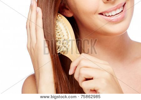 Close-up of young smiling brunette brushing her long hair