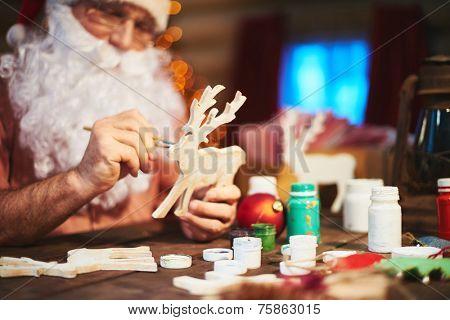 Senior Santa man painting wooden deer with gouache