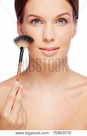 Fresh girl touching her cheek with powder brush