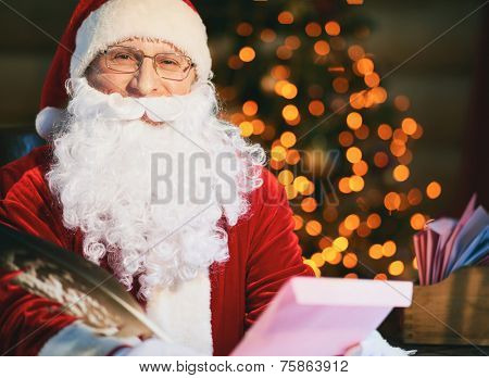 Portrait of Santa Claus reading and answering Christmas letters