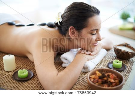 Portrait of pretty young female relaxing in spa salon