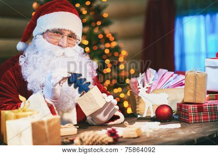 Happy Santa Claus looking at camera while putting blue toy fiirtree into giftbox