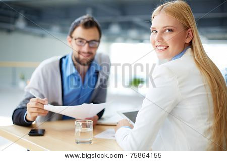 Friendly businesswoman looking at camera with her co-worker on background
