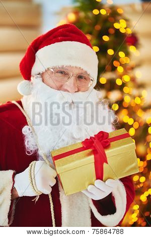 Portrait of happy Santa Claus with golden giftbox looking at camera