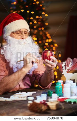Senior man in Santa cap and beard painting toy ball with gouache before xmas