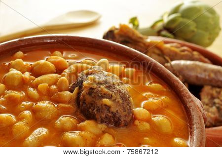 an earthenware bowl with potaje de judias y garbanzos, a traditional spanish legume stew