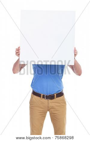 picture of a young casual man holding a blank board in front of his face. isolated on a white background