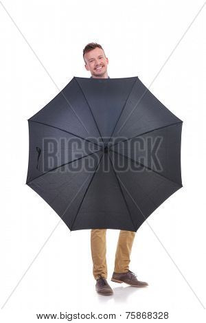 full length picture of a young casual man holding an umbrella in front of him and smiling for the camera. isolated on a white background