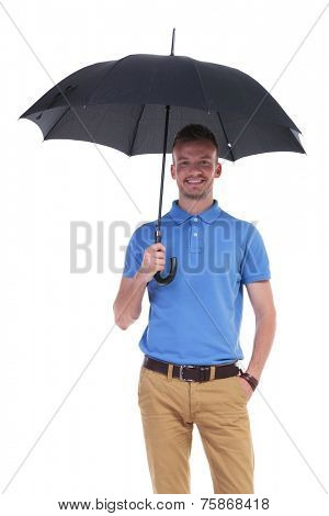 picture of a young casual man holding a black umbrella while holding his other hand in his pocket and smiling for the camera. isolated on a white background