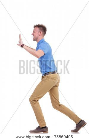 full length side view picture of a young casual man pushing something imaginary with great difficulty. isolated on a white background