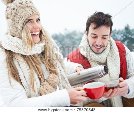 Happy woman pouring man tea from thermos jug in winter