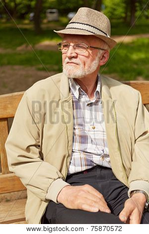 Old man with hat and glasses sitting on park bench in summer