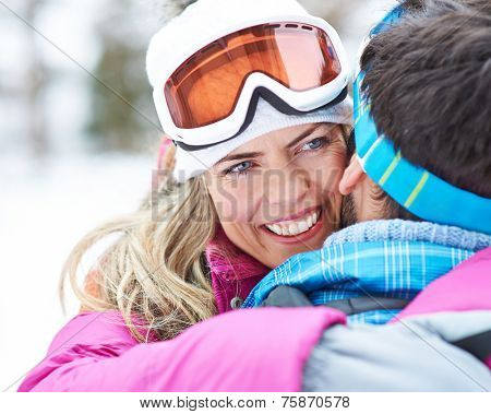 Happy Woman embracing man on ski trip in their winter holiday