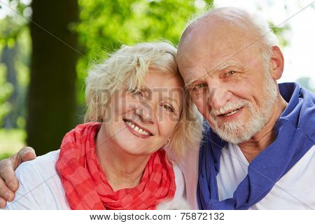 Old man and woman as senior couple in nature in fall