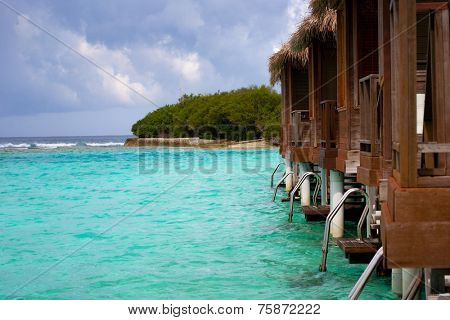 Wooden chalets over water in tropical island