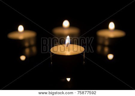 Four Tea Candles with Reflection on Black