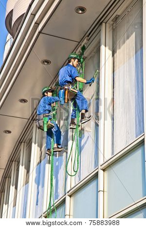 TOKYO, JAPAN- OCTOBER 28, 2014: Workers cleaning windows service on high rise building on October 28, 2014. in Tokyo, japan.