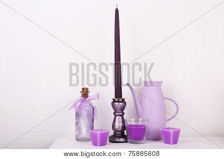 Candles in candle holders on table on white background