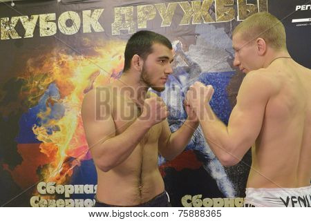 NOVOSIBIRSK, RUSSIA - NOVEMBER 7, 2014: Kasum Kasumov (left) and Alexander Matmuratov posing against the poster of the Friendship Cup, The competitions include 10 kinds of martial arts
