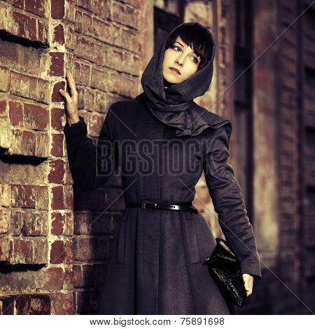Sad young fashion woman in grey classic coat at the wall