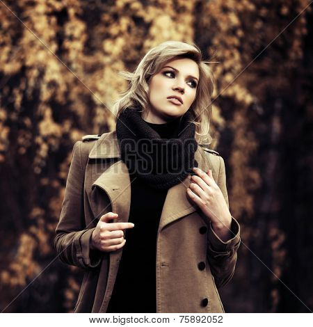 Happy young blond fashion woman walking in autumn forest
