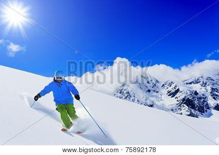 Skiing, Skier, Freeski, Freeride in fresh powder snow - man skiing downhill