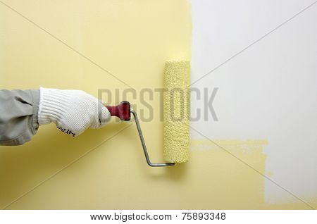 Hand painting a white wall with a paint roller
