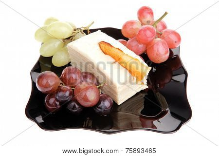 raw grapes and cream cake on black over white