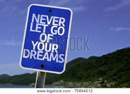 Never Let Go Of Your Dreams sign with a beach on background