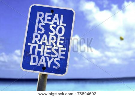 Real is So Rare These Days sign with a beach on background