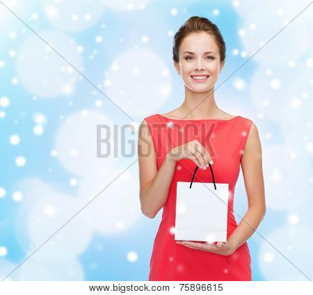 shopping, sale, christmas, holidays and people concept - smiling elegant woman in red dress with small shopping bag over blue lights and snow background
